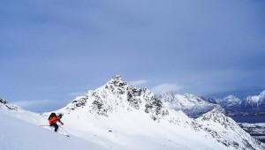 Mann i orange jakke kjører på ski