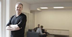 En smilende Espen Grepperud med armene i kors i et kontormiljø