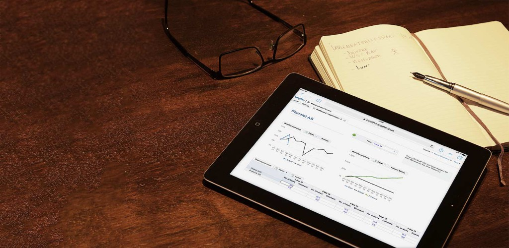 Ipad som viser Anaplan i bruk,, ligger på et skriverbord sammen med penn, notatblokk og briller