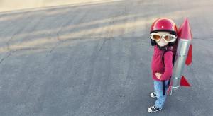 Gutt med rød genser, rød hjelm og flybriller, med rakett på ryggen.