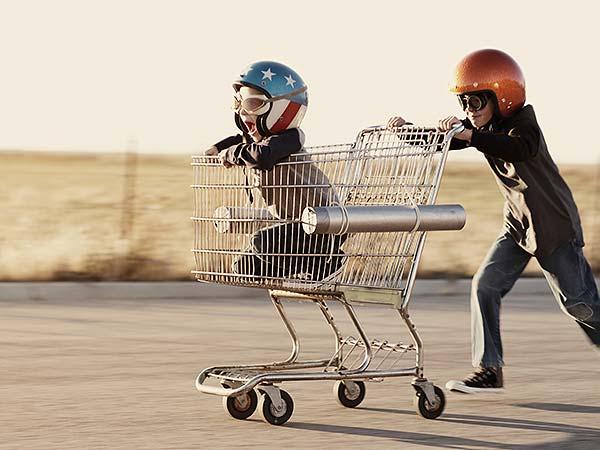Gutt med hjelm dytter en handlevogn med en annen gutt med hjelm oppi