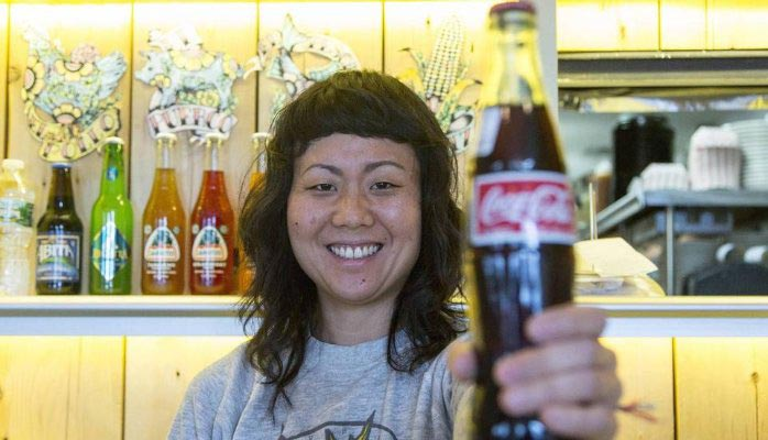 Smilende mexikansk dame med svart hår holder frem en Coca Cola flaske. Foto: Kristoffer Rønneberg / Aftenposten